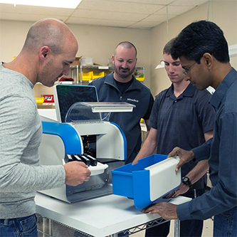 Ximedica Los Gatos employees working on a medical device machine