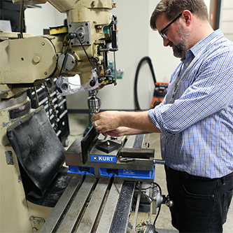 Ximedica Minneapolis employee working on manufacturing machine
