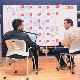 Two Ximedica San Francisco employees in a brainstorm meeting with a concept generation wall